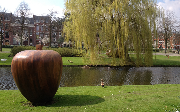A photograph of a sculpture of an apple at the side of a river in Rotterdam, the Netherlands.